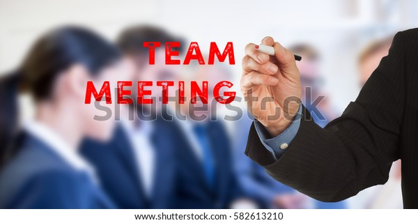 Team Meeting, Male hand in business wear holding a thick pen, writing on an imaginary screen at the camera, business team in background, digital composing.