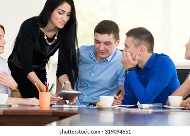 Team members listening attentively to a business woman brunette holding a presentation.