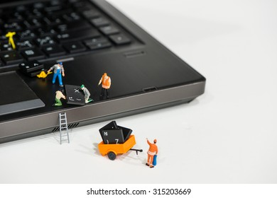 Team of Miniature workers repairing Laptop