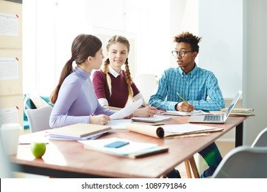 Team of modern students of college or high school having discussion of home assignment while preparing it