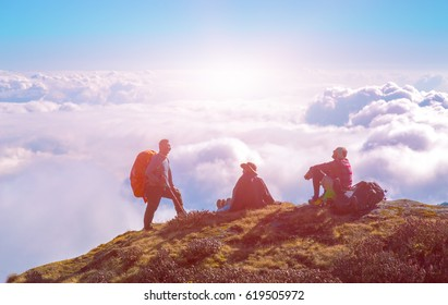 Team of Mountain Hikers relaxing on high Cliff above Cloud Level and enjoying warm Sunshine