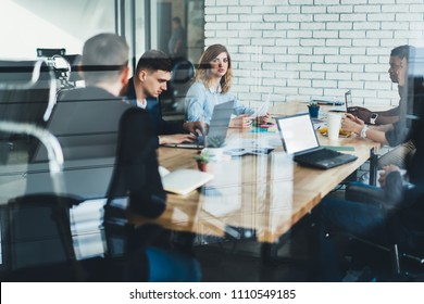 Team of multicultural male and female professionals dressed in formal wear discussing productive strategy together with proud ceo sitting at meeting table in stylish office interior behind glass wall
