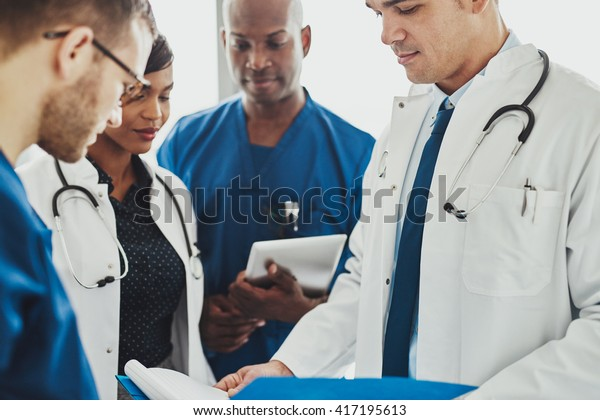 Team of multiracial doctors standing reading patient records on a ward round in a hospital, close up view of diverse men and women