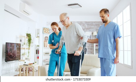 Team of nurses or social workers helping an old disabled man to walk with his crutches out of the nursing home room.