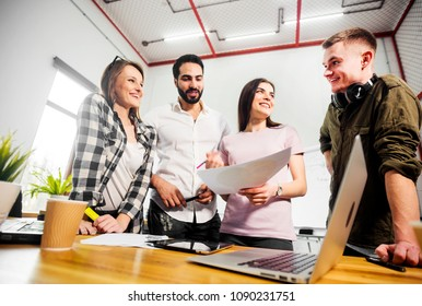 Team of office workers discussing diagrams before flip chart board, indoor shot in modern office