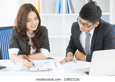 Team of office workers discussing possible strategic movements and analyzing statistics