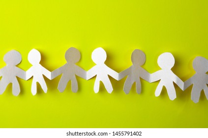 Team of paper chain cutout people in a row on yellow background holding hands