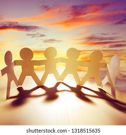 Team of paper chain people holding hands in front of bright sky
