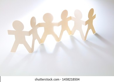 Team of paper chain people in a row holding hands. Copy space