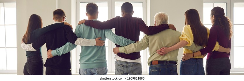 Team of people hug standing in a row with their backs to the camera and looking out the window. People of all ages and nationalities show their support for each other and equality. Concept of unity.