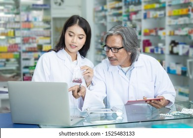 Team pharmacists colleague concentrate with pills senior man with blonde hair apothecary advice or discussing medicines with young Asian attractive colleague in drugstore blurred background
