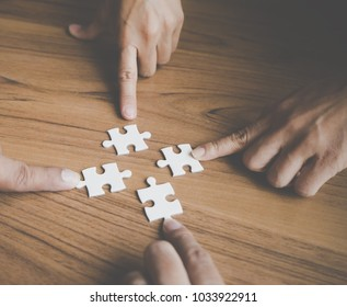 Team placing four puzzles jigsaw together for team concept