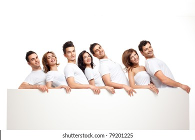 team of playful smiling people holding banner