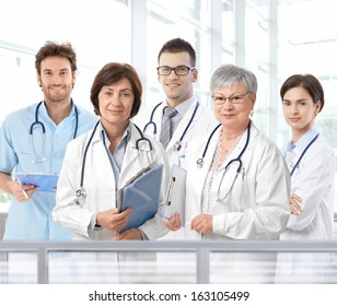 Team portrait of mixed aged medical doctors standing in hospital lobby, looking at camera, smiling.