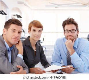 Team portrait of young businesspeople working together, sitting at desk, looking at camera.