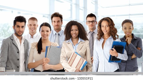 Team portrait of young and successful business people looking at camera, smiling.