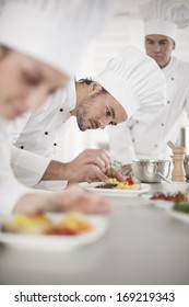 Team preparing dishes in a professional kitchen focus on a cook