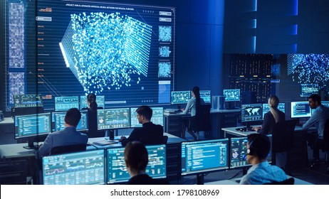 Team of Professional Computer Data Science Engineers Work on Desktops with Screens Showing Charts, Graphs, Infographics, Technical Neural Network Data and Statistics. Dark Control and Monitoring Room.