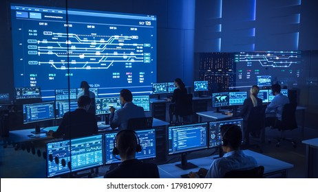 Team of Professional Computer Data Science Engineers Work on Desktops with Screens Showing Charts, Graphs, Infographics, Technical Neural Data and Statistics. Low Key Control and Monitoring Room.