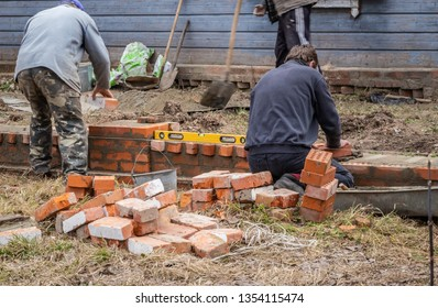 A team of professional craftsmen builds a house of brick and wood in the countryside.