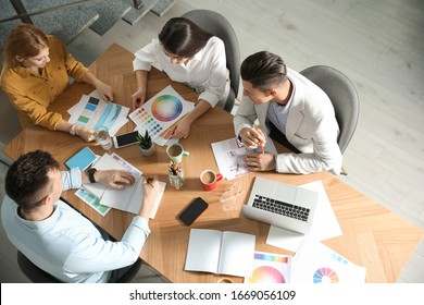 Team of professional designers working together at table in office