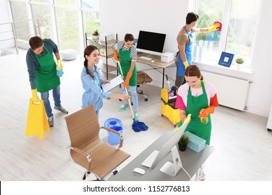 Team of professional janitors in uniform cleaning office
