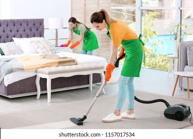 Team of professional janitors in uniform cleaning bedroom