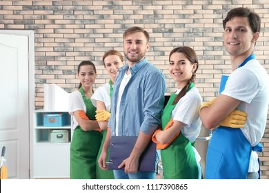 Team of professional janitors in uniform indoors