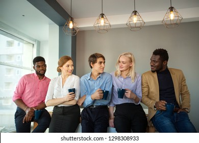 team of professional managers at work in the office during a break with cups of coffee