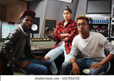 Team of professional musicians or sound operators sitting in studio of music production