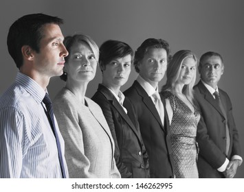 Team of professionals looking at colleague against gray background