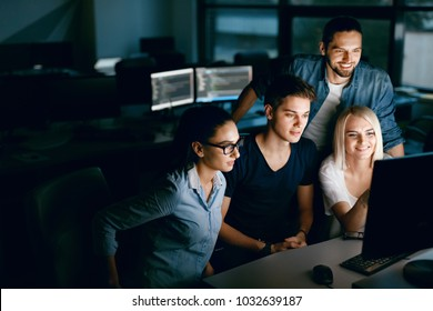 Team Of Programmers Working On Computer In Office. Young Beautiful People Working On Project Together In IT Office In Evening, Looking At Monitor, Sitting In Dark. Programming. High Resolution.