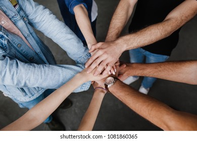 Team put hands together, show connection and alliance, Teambuilding in office, young businessmen and women in casual unite hands for teamwork and cooperation at new project.
