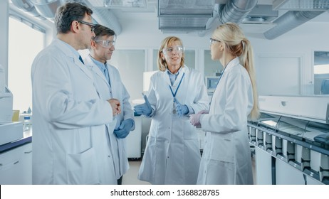 Team of Research Scientists Have Meeting, They Have Discussion While Standing in the Middle of Laboratory. People in Innovative Modern Lab Doing Genetics and Pharmaceutical Studies.