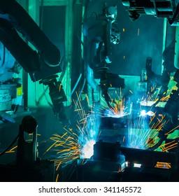 Team Robot welding movement Industrial automotive part in factory