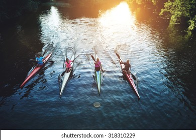 Team of rowing people sailing against camera in sunset