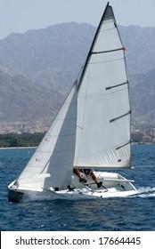 Team sailing on a small sail boat