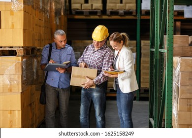 Team of sale managers and warehouse worker checking list and inventory on the shelf in storehouse.
