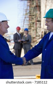 A team of shipping engineers in front of an oil platform in the harbor, with two shaking hands in the foreground