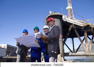 A team of shipping engineers in front of an oil platform in the harbor