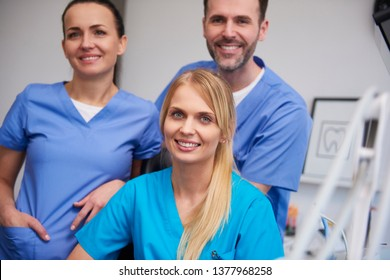 Team of smiling and satisfied dentists in dentist's office