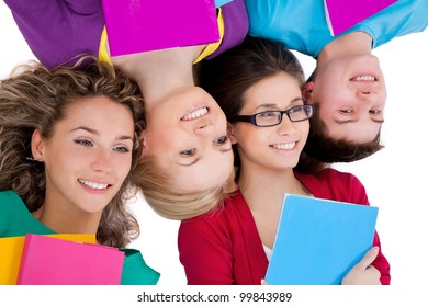 Team of smiling students lying in line and holding the books