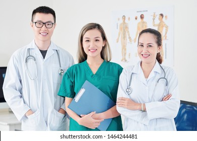 Team of smiling Vietnamese general practitioner, syrgeon and orthopedic surgeon standing in modern medial office