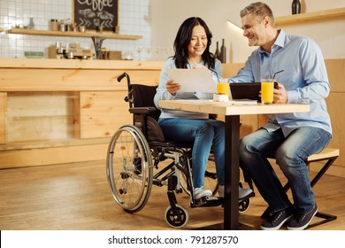 Team spirit. Beautiful exuberant disabled woman and a handsome cheerful blond man smiling and discussing work while sitting in cafe