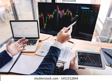 Team of stockbrokers Discussing with display screens Analyzing data, graphs and reports of stock market trading for investment