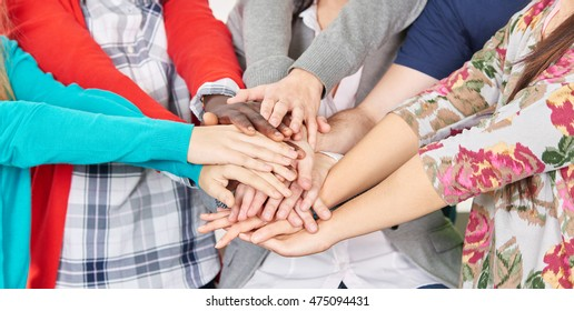 Team of students put their hands together to motivate themselves