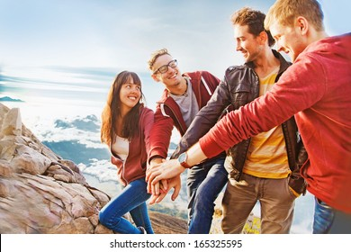 team success concept: group of people holding hands on the top of the mountain