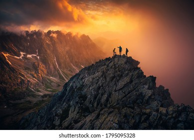 Team success concept photo, friends standing together on the top of the hill, over beautiful mountains landscape in gold sunset light, orange edit space