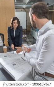 team of successful architects working with building plans together at office