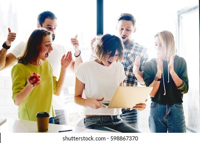 Team of successful freelancers is celebrating the receiving of positive answer from the investors. Group of young entrepreneurs are happy with the good news from the business partners.